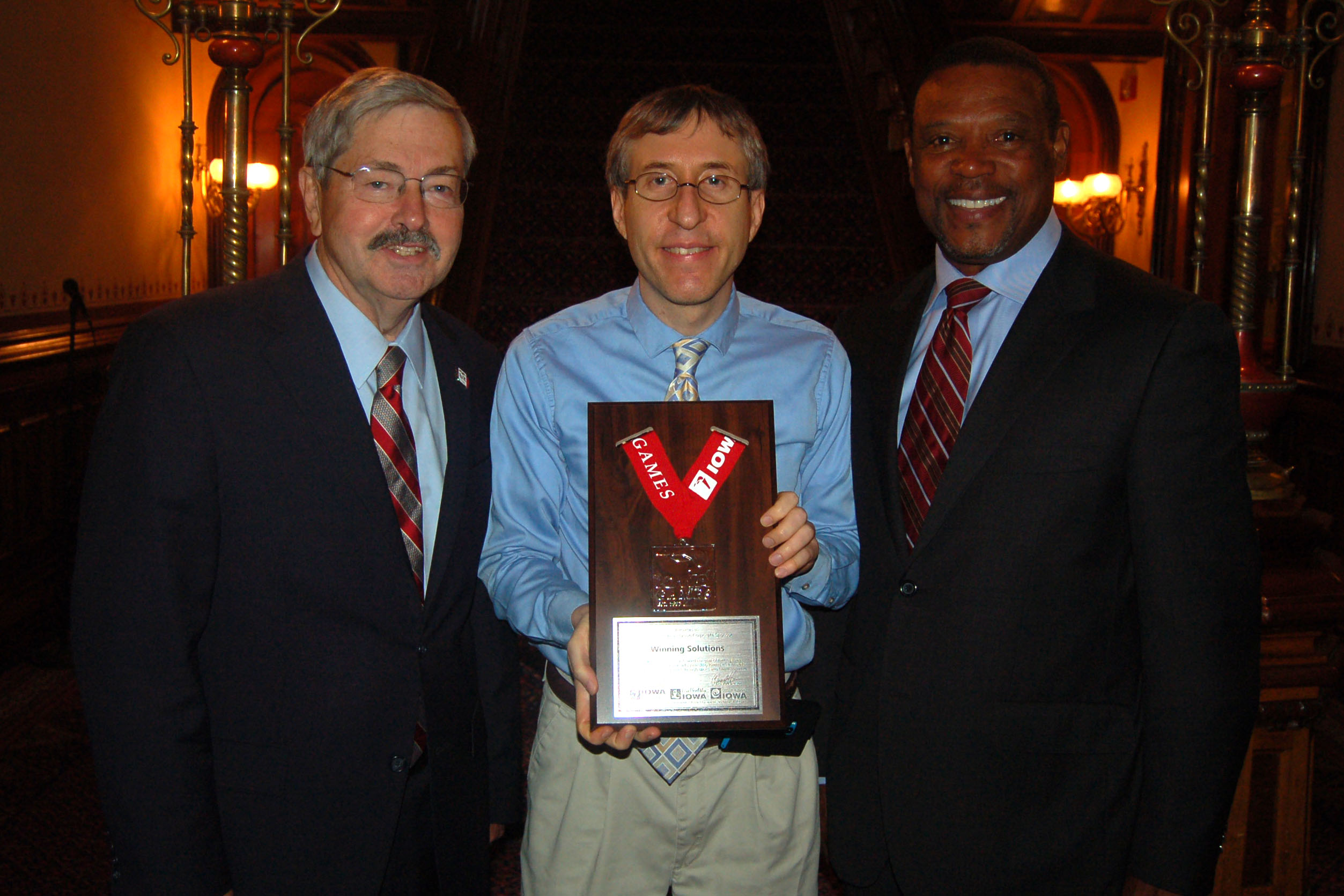 Mark Steffen (center) of Winning Solutions, Inc. is pictured accepting a plaque recognizing WSI's service to the Iowa Sports Foundation from Former Governor Terry Branstad (left) Former Iowa Governor Clarence Hudson (Right), among others was in attendance.